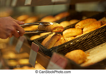 hand with tongs taking bun at bakery or grocery - food,...