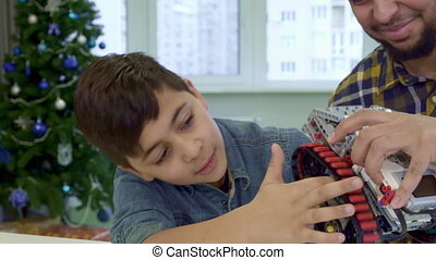 Boy puts his forefinger under the track of toy ATV - Little...