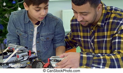 Father and son examine toy tracked ATV