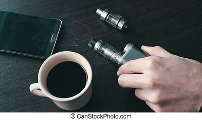 businessman with an e-cigarette on the stylish table - young...