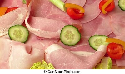 Food tray with delicious salami, pieces of sliced ham, tomatoes, salad and vegetable