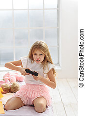 Excited girl playing game console - I must win. Full of...