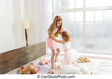 Happy girls playing in princesses - Joyful two sisters are...