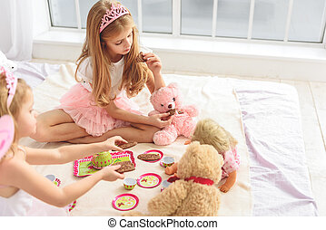 Cute children treating toys with sweets