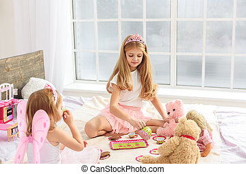 Cute sisters having tea party in bedroom