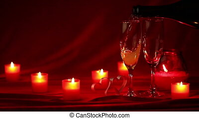 Champagne and candles - Pouring champagne in glasses at...