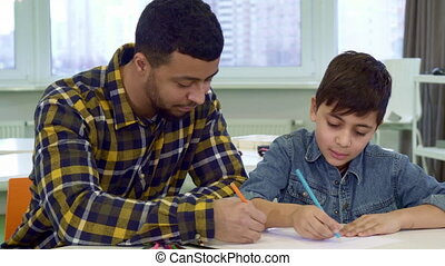 Father and son draw at the table - Attractive father and son...