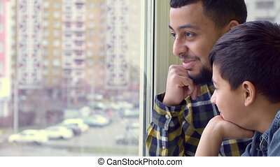 Father and son look out the window - Attractive father and...