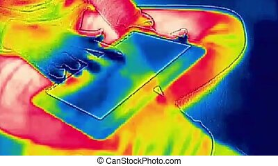 Young woman uses a Tablet - Infrared thermal video while...