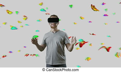 Man with VR gear glasses within butterfly cloud interactive...