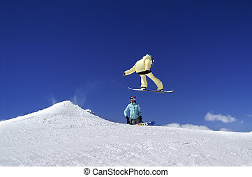 Two snowboarders in terrain park at ski resort on sun winter day