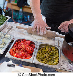 Chef making pita bread for falafel roll outdoor on street stall.