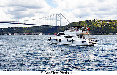 White luxury yacht / boat crosses Bosphorus between European and Asian sides in Istanbul. It is cloudy autumn day. FSM (Fatih Sultan Mehmet) bridge is in the background.