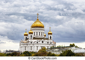 Cathedral of Christ the Saviour under dramatic clouds in Moscow. Gleaming domes top this Catholic edifice, rebuilt in the 1990s, with ornate, fresco-lined interior.