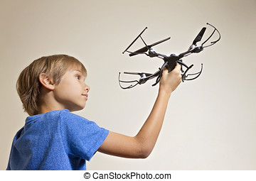 Schoolboy kid playing with drone. Boy holding quadcopter in...