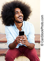 happy man sitting on steps with mobile phone laughing -...