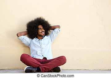 smiling man sitting on floor leaning on wall - Full body...