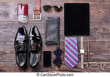 Men's accessories on wooden background. Black shoes and bow...