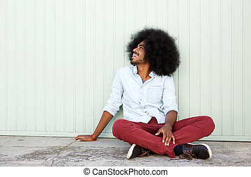 cheerful man sitting outside on floor by wall - Full body...