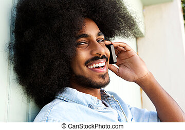 happy afro man talking on mobile phone and smiling - Close...