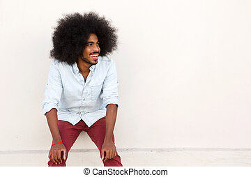 young man laughing with hands on knees and afro - Portrait...