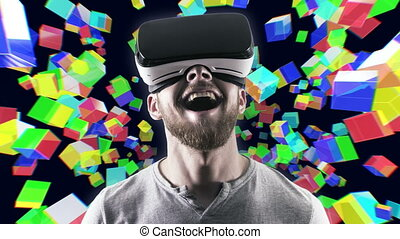 Emotional smile happy man wearing virtual reality goggles. VR headset. Within virtual space cubes black look up