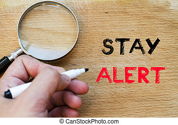 Stay alert text concept - Human hand over wooden background...