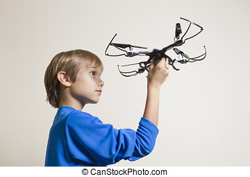Little kid holding the drone, preparing for take off - Boy...