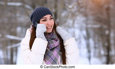 Young woman talking mobile phone and laughing in winter park