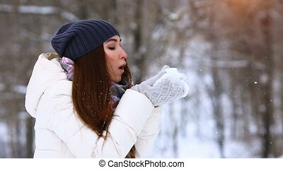 Winter girl blowing snow. Beauty Joyful Teenage Model Girl having fun in winter park. Beautiful young woman laughing outdoors. Enjoying nature.