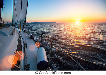 Yacht at sailing regatta at the sea during sunset. Luxury boats.