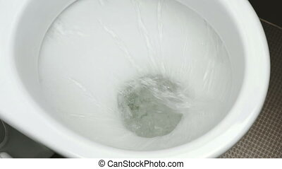 Close up view of flushing white toilet. Cleaning of the...
