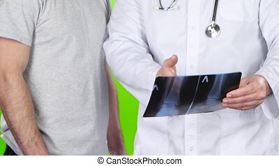 Male doctor and a man patient discussing roentgenogram. Green screen