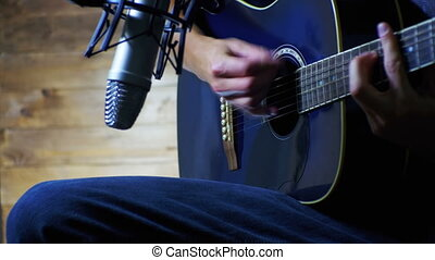 Musician Recording Acoustic Guitar in Microphone on the Home Studio