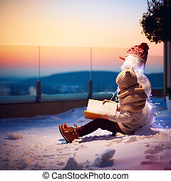 winter fairy tale. young boy, kid reading interesting book to his friend snowman at the backyard