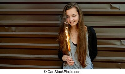 Young Latino women against brown wall with sparkler having...