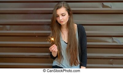 Pensive woman holding sparkler in her hands on the street in front of brown wall, slow-motion shot, retro color.