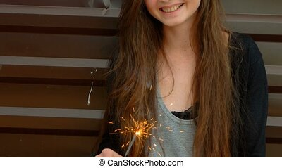 Young happy woman with fire sparkler in her hands, looking...