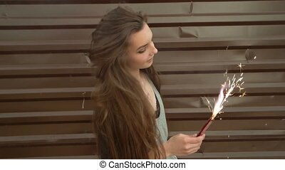 Beautiful smiling woman holding a sparkler on a New Year's Eve. Slow-motion footage