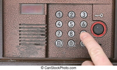 Person push buttons on a panel of intercom system - The...
