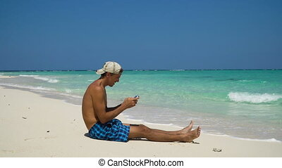 Man with the tablet on the beach