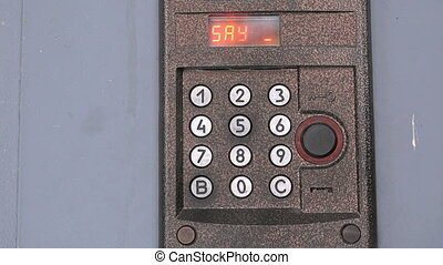 Person pushing buttons on the panel of intercom