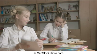 Children or two happy girls learning and doing homework in school classroom