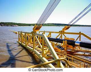 Laying of pipes with pipe-laying barge crane near the shore.