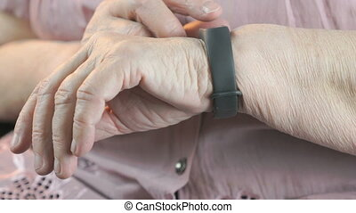 The elderly woman using the smart fitness tracker - Black...