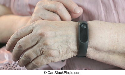 The old woman using the wristband fitness tracker