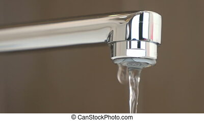 Water under weak pressure flows from a water tap - The tap...