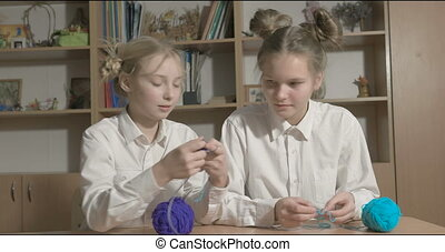 Two girls learn to knit in the classroom or room.