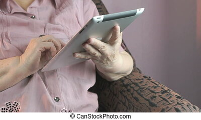 The old woman holding the silver tablet computer