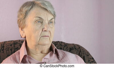 Elderly woman looks in the direction indoors